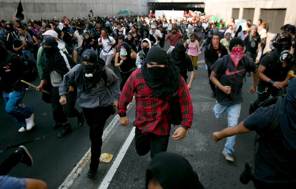 . Masked protesters run during a march commemorating the anniversary of the Tlatelolco massacre in Mexico City, Wednesday, Oct. 2, 2013. Mexico commemorated the 45th anniversary of the massacre of students holding an anti-government protest, killed by men with guns and soldiers in 1968 days before the Summer Olympics celebrations in Mexico City. (AP Photo/Eduardo Verdugo)