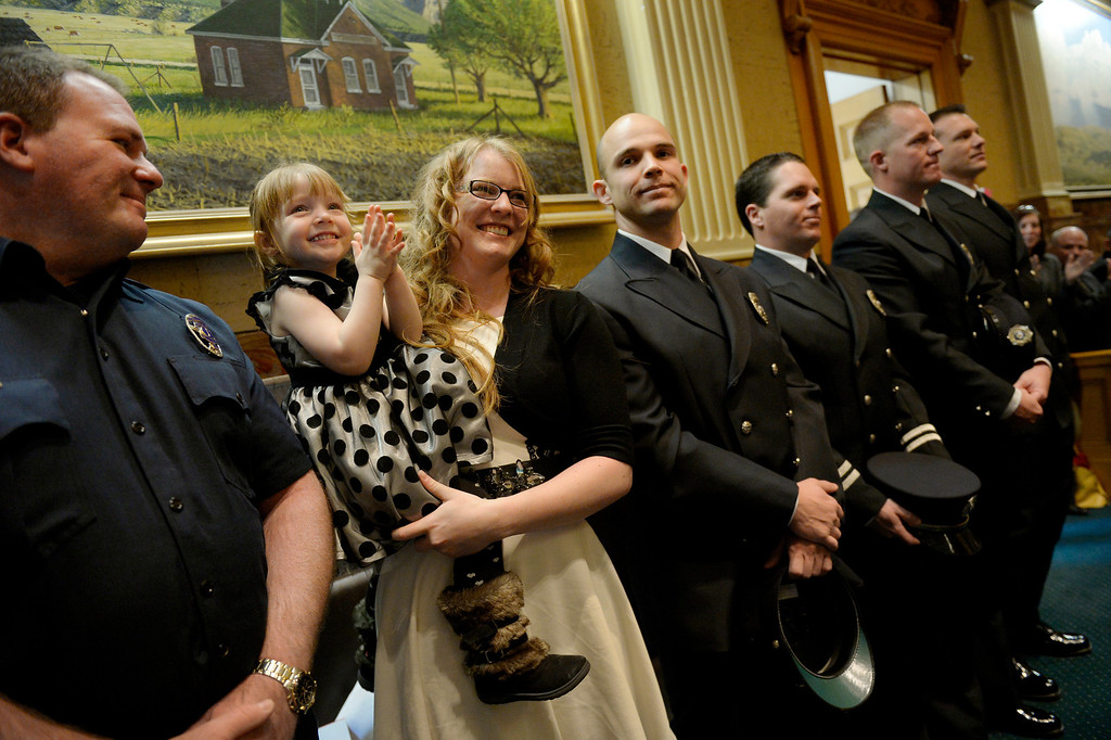 """. DENVER, CO. - JANUARY 08: Erin Brazzil stands with her daughter, Autumn, 3, and first responders (l-r) Mike Becker, of the Longmont Fire Department and Sean Tallman, Chad Rademacher, James Wood and Steve Knoll of the Mountain View Fire Department in the House of Representatives during the first day of the new legislative session at the Colorado Capitol in Denver, CO January 08, 2014. House Speaker Mark Ferrandino recognized the firefighters for saving Brazzil from her water engulfed car in Longmont during flooding on September 12, 2013. In his speech Ferrandino told their story, \""""On September 12th Erin Brazzil was driving across Longmont to pick up her young daughter when a wall of water engulfed her Nissan Altima. It lost power and began to fill with water. She called 9-1-1.  When several rescuers,including Lieutenant Mike Becker and his crew from the Longmont Fire Department, were finally able to locate the car, it was barely visible,nearly submerged.Erin�s breathing space had been reduced to a few inches at the roof of the car.  Three members of the Mountain View Fire Rescue-- Captain Chad Rademacher, Steve Knoll and Sean Tallman � struggled through the rising waters to reach the car.  The responders had to pry off the windshield and lift Ms. Brazzil out of the car, and Mountain View fire medic Jamie Wood, riding a personal watercraft � that�s right, a Jetski � took her to safety.   Erin and her rescuers are with us today. Please join me in thanking all the first responders who showed such ingenuity and bravery during the storms.  Without them, it�s unimaginable how much worse it could have been.\"""" (Photo By Craig F. Walker / The Denver Post)"""