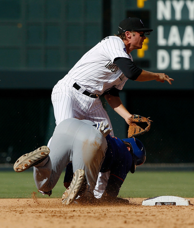 . New York Mets\' Anthony Recker, right, barrels into Colorado Rockies second baseman Josh Rutledge after being forced out at second base in the fifth inning of a baseball game in Denver on Thursday, June 27, 2013. The Mets scored a run on the play. (AP Photo/David Zalubowski)