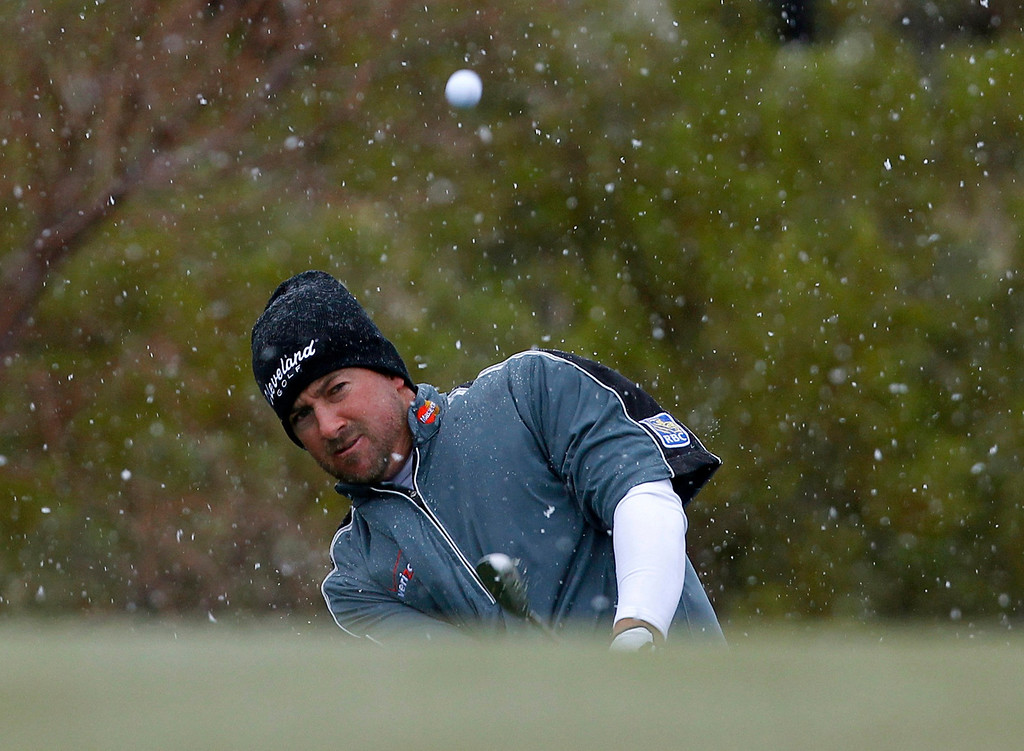 . Graeme McDowell of Northern Ireland hits to the first green as snow falls in the desert during the first round of the WGC-Accenture Match Play Championship golf tournament in Marana, Arizona February 20, 2013. REUTERS/Matt Sullivan