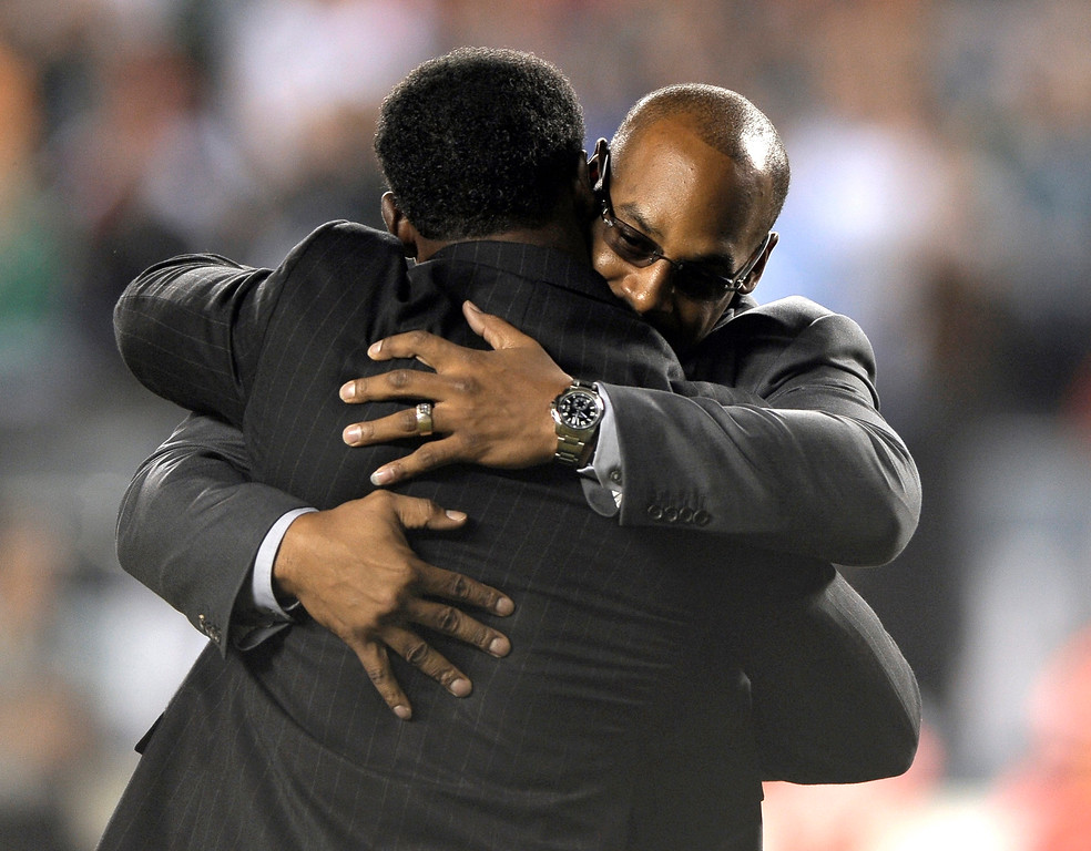 . Former Philadelphia Eagles Donovan McNabb, rear, and Brian Dawkins embrace during halftime of an NFL football game between the Eagles and the Kansas City Chiefs, Thursday, Sept. 19, 2013, in Philadelphia. The Eagles retired McNabb\'s jersey number at halftime.  (AP Photo/Michael Perez)
