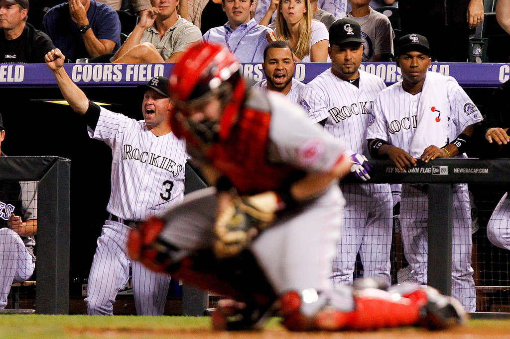 . Colorado Rockies\' Michael Cuddyer (3), left, and teammates react to double by Charlie Culberson, scoring two, during the fourth inning of a baseball game against the Cincinnati Reds, Friday, Aug. 30, 2013, in Denver. (AP Photo/Barry Gutierrez)