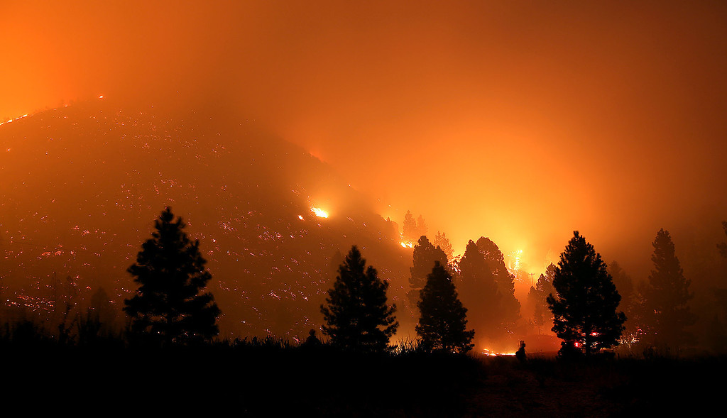 . In this Monday night Aug. 12, 2013 photo, firefighters start a back burn along the Pine-Featherville Road while battling the more than 90,000-acre Elk Fire Complex near Pine, Idaho. Fire crews in central Idaho capitalized on favorable winds Tuesday to continue burnout operations around a small mountain community, seeking to push a wildfire toward an area torched by a massive blaze last year. (AP Photo/The Times-News, Ashley Smith)