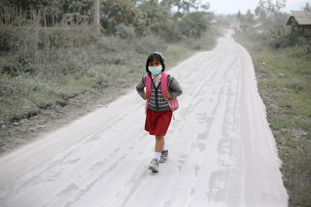 . A student walks on a road covered with volcanic ash from the eruption of Mount Sinabung in Tiga Nderket, North Sumatra, Indonesia, Wednesday, Nov. 6, 2013. (AP Photo/Binsar Bakkara)
