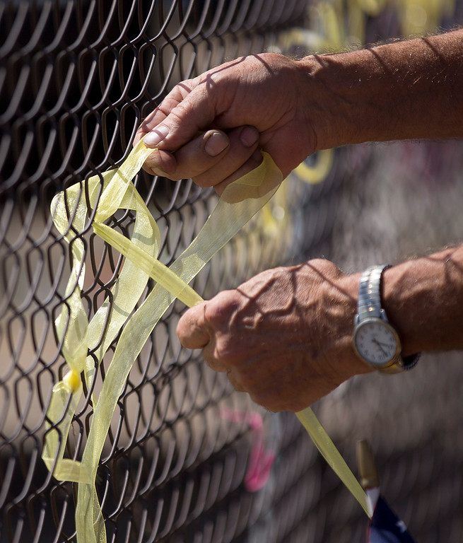 . Dave Anderson ties a yellow ribbon into the shape of a heart on the fence outside the Granite Mountain Interagency Hotshot Crew fire station, Tuesday, July 2, 2013 in Prescott, Ariz.  (AP Photo/Julie Jacobson)