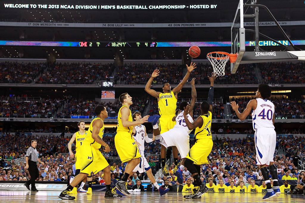 . ARLINGTON, TX - MARCH 29:  Elijah Johnson #15 of the Kansas Jayhawks goes up against the defense of Glenn Robinson III #1 and Tim Hardaway Jr. #10 of the Michigan Wolverines in the first half during the South Regional Semifinal round of the 2013 NCAA Men\'s Basketball Tournament at Dallas Cowboys Stadium on March 29, 2013 in Arlington, Texas.  (Photo by Ronald Martinez/Getty Images)