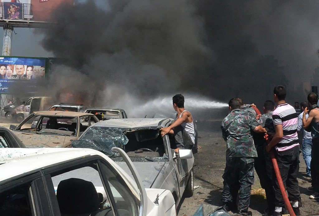 . Lebanese fire fighters extinguish burned cars at an explosion site outside a mosque, in the Northern city of Tripoli, Lebanon, Friday, Aug. 23, 2013.  (AP Photo)