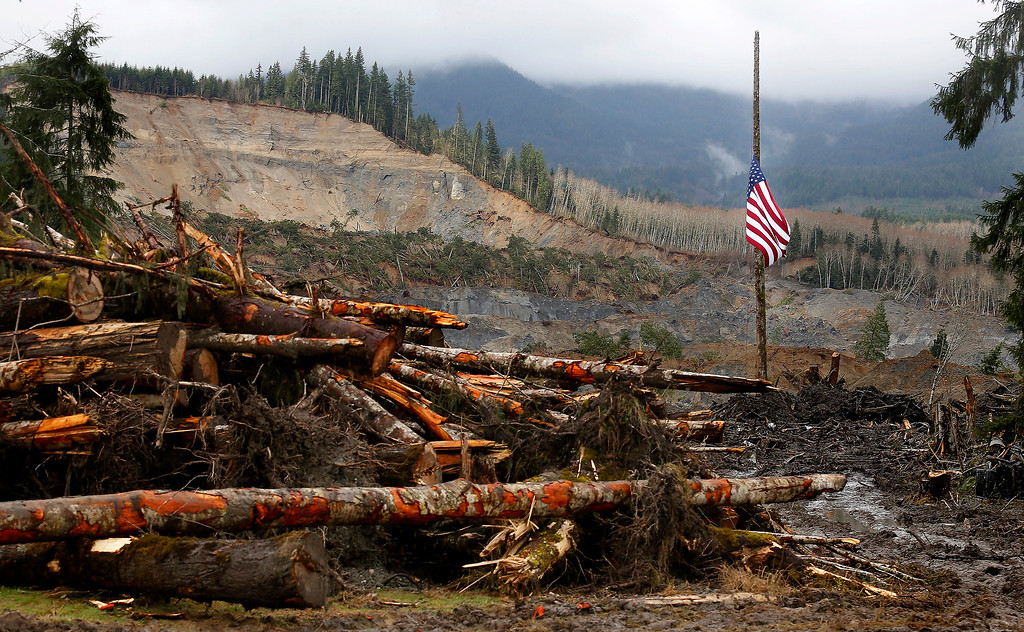 . A large American flag hangs at half mast from a post at the mudslide site near Oso, Wash., Sunday, March 30, 2014. (AP Photo /The Herald, Annie Mulligan)