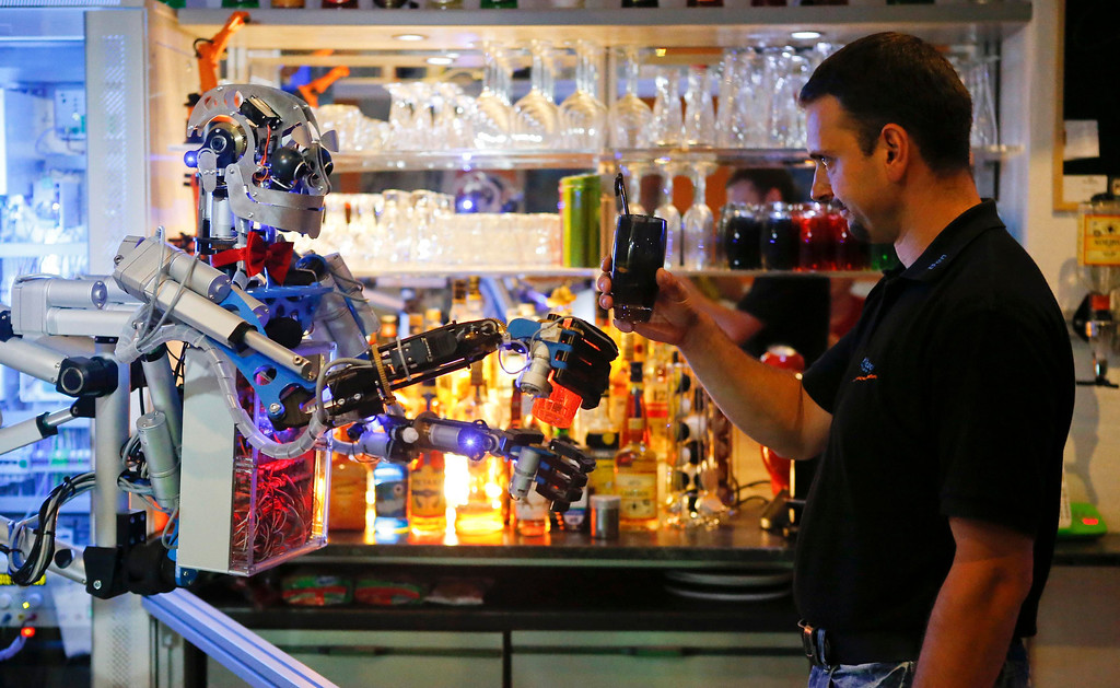 """. Mechatronics engineer Ben Schaefer (R) interacts with humanoid robot bartender \""""Carl\"""" as it prepares a drink for a guest at the Robots Bar and Lounge in the eastern German town of Ilmenau, July 26, 2013. The Humanoid robot bartender \""""Carl\"""", developed and built by Schaefer who runs a company for humanoid robots, prepares spirits for the mixing of cocktails and is able to interact with customers in small conversations. Picture taken July 26, 2013. REUTERS/Fabrizio Bensch"""