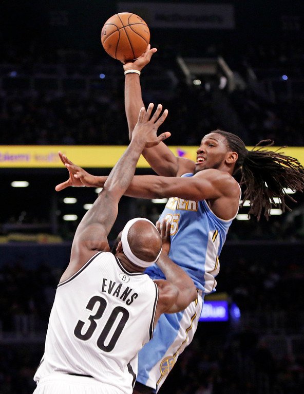 . Denver Nuggets forward Kenneth Faried, right, shoots over Brooklyn Nets forward Reggie Evans (30) in the second half of an NBA basketball game Tuesday, Dec. 3, 2013, in New York. The Nuggets won 111-87. (AP Photo/Kathy Willens)