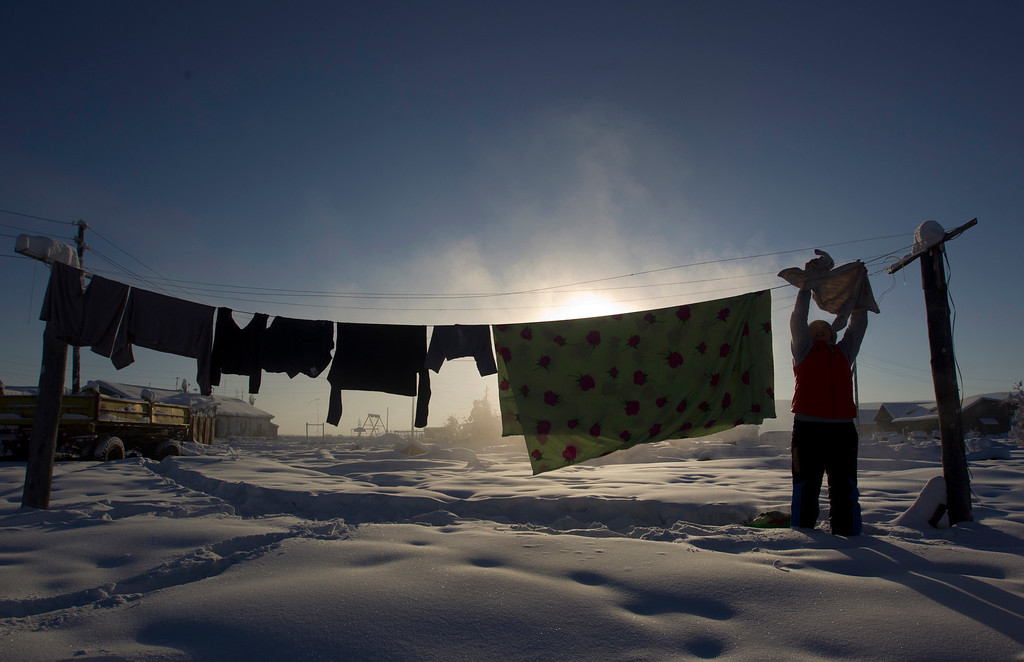 . Sargylana Mozhukova, 35, hangs washing in the village of Tomtor in the Oymyakon valley in northeast Russia, February 2, 2013. The coldest temperatures in the northern hemisphere since the beginning of the 20th century have been recorded in the Oymyakon valley, known as the \'Pole of Cold\', where according to the United Kingdom Met Office a temperature of -67.8 degrees Celsius (-90 degrees Fahrenheit) was registered in 1933.     REUTERS/Maxim Shemetov