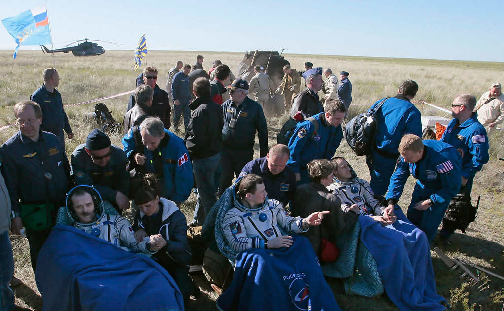 . U.S. astronaut Tom Marshburn (R), Russian cosmonaut Roman Romanenko (C) and Canadian astronaut Chris Hadfield sit after leaving the Russian Soyuz space capsule following its landing some 150 km (90 miles) southeast of the town of Zhezkazgan, in central Kazakhstan May 14, 2013.  REUTERS/Mikhail Metzel/Pool
