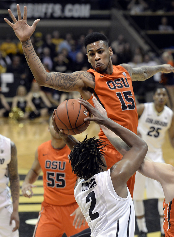 . Oregon State\'s Eric Moreland tries to block the shot of Colorado\'s Xavier Johnson during an NCAA college basketball game Thursday, Jan. 2, 2014, in Boulder, Colo. Jeremy Papasso/Daily Camera