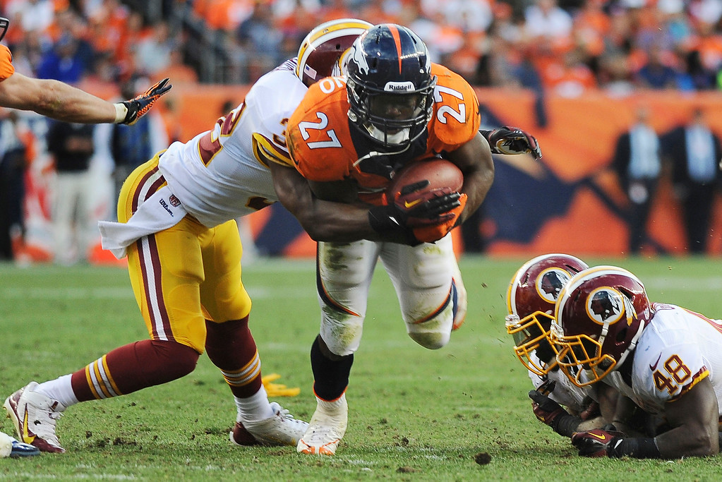 . Denver Broncos running back Knowshon Moreno fights for extra yardage against the Washington Redskins in the fourth quarter at Sports Authority Field. (Photo by Steve Nehf/The Denver Post)