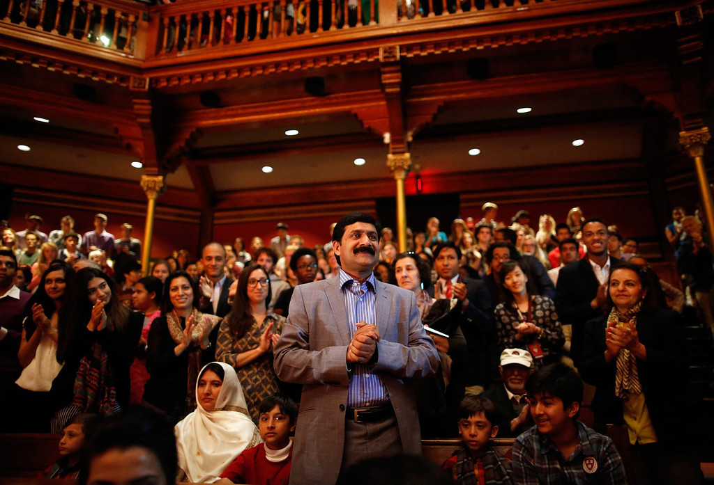 . Malala Yousafzai\'s father Ziauddin Yousafzai stands as he is given a standing ovation at Harvard University Friday, Sept. 27, 2013, on the school\'s campus in Cambridge, Mass.  Malala Yousafzai, a Pakistani teenager and an advocate for education for girls, survived a Taliban assassination attempt last year on her way home from school.  (AP Photo/Jessica Rinaldi)