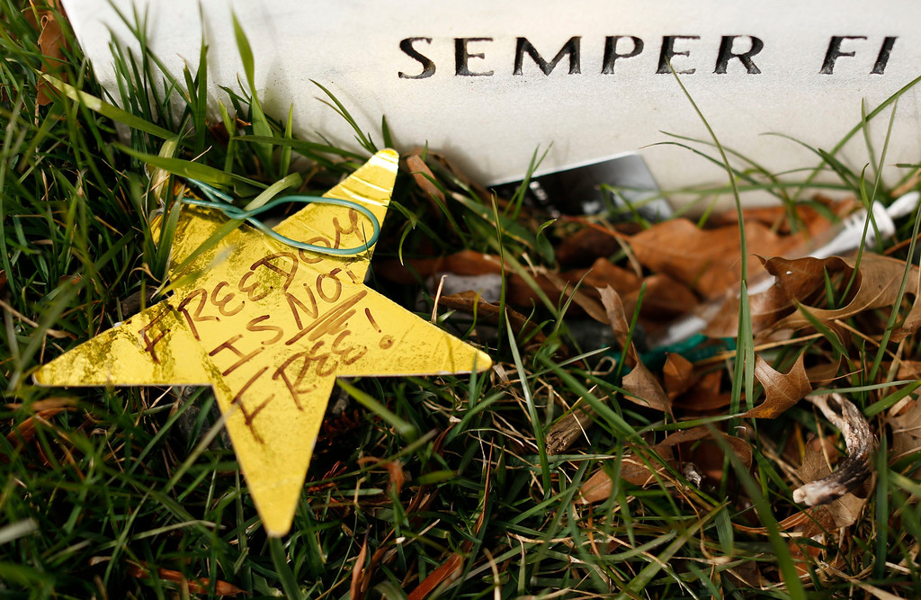 """. A star written with \""""Freedom is Not Free!\"""" is seen beside a headstone in Section 60 at Arlington National Cemetery in Virginia, March 13, 2013. Section 60 contains graves of soldiers from the wars in Iraq and Afghanistan. Picture taken March 13, 2013. REUTERS/Kevin Lamarque"""