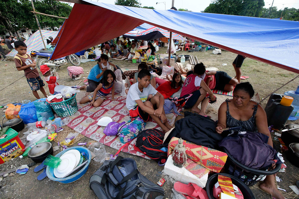 . Residents camp out in a park to avoid aftershocks at Loon township, Bohol province in central Philippines Wednesday Oct. 16, 2013.  (AP Photo/Bullit Marquez)