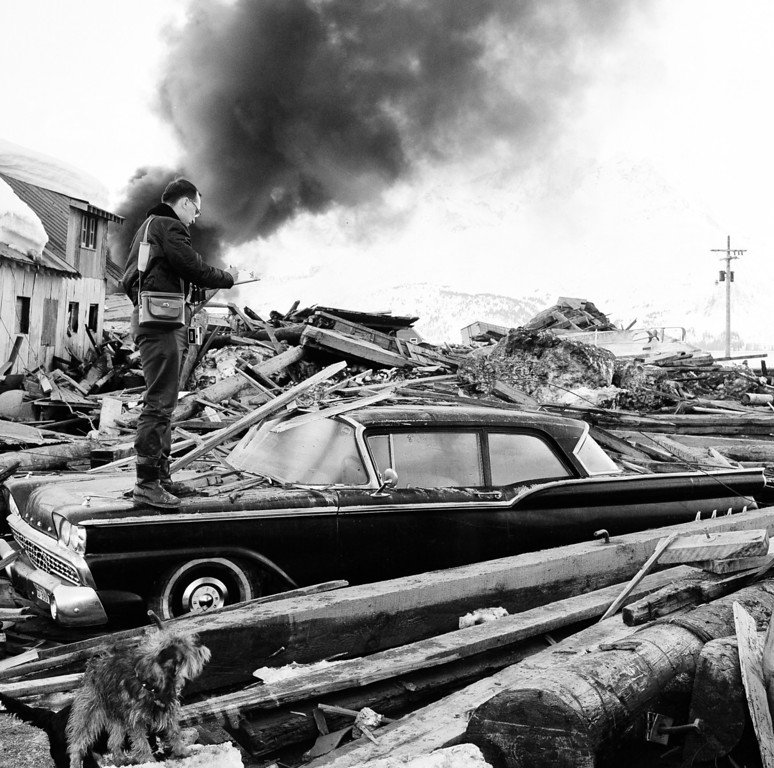 . A photographer looks over wreckage as smoke rises in the background from burning oil storage tanks at Valdez, Alaska, March 29, 1964.  The city was hit hard by the earthquake that demolished some of Alaska\'s most picturesque and largest cities.  (AP Photo)