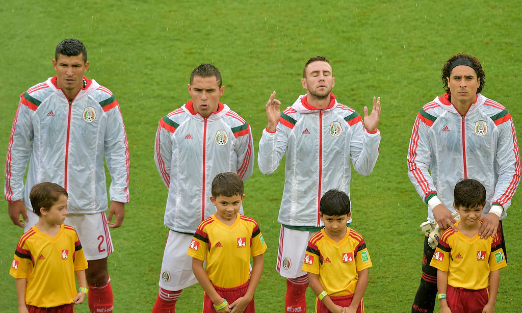. (L-R) Mexico\'s defender Francisco Rodriguez, defender Paul Aguilar, defender Miguel Layun and goalkeeper Guillermo Ochoa listen to their national anthem before the start of a Group A football match between Mexico and Cameroon at the Dunas Arena in Natal during the 2014 FIFA World Cup on June 13, 2014. GABRIEL BOUYS/AFP/Getty Images