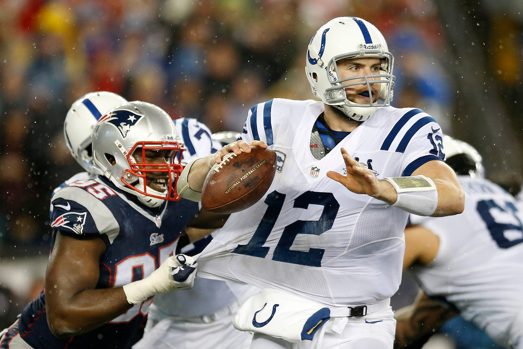 . New England Patriots defensive end Chandler Jones (95) grabs the jersey of Indianapolis Colts quarterback Andrew Luck (12) as Luck looks for an opening to pass during the first half of an AFC divisional NFL playoff football game in Foxborough, Mass., Saturday, Jan. 11, 2014. (AP Photo/Michael Dwyer)