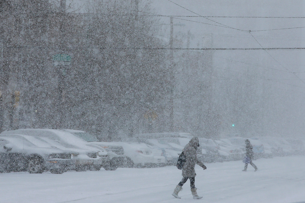 . Pedestrians walk through a snow storm, Tuesday, Jan. 21, 2014, in south Philadelphia. (AP Photo/Matt Slocum)