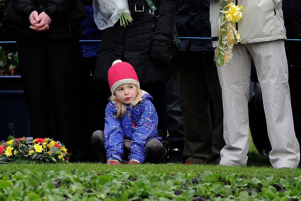 . A young girl crouches at her mothers\' feet during the memorial service in Dryfesdale cemetery to commemorate the 25th anniversary of the air disaster on December 21, 2013 in Lockerbie, Scotland.  (Photo by Ian Forsyth/Getty Images)