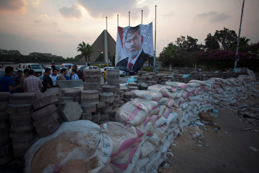 . Supporters of Egypt\'s ousted President Mohammed Morsi stand behind sand barriers recently set up where supporters of Morsi have installed a camp and held daily rallies outside Rabaah al-Adawiya mosque in Cairo, Egypt, Tuesday, Aug. 13, 2013. Instead of rushing for the exits, Islamist supporters of Egypt\'s ousted president are replacing tents with wooden huts in their sprawling Cairo encampment. Barbershops have sprung up and many tents now have satellite dishes. (AP Photo/Khalil Hamra)