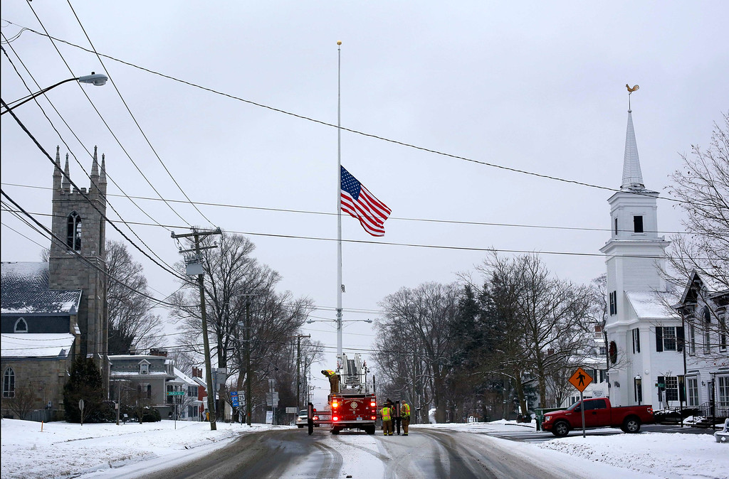 . On the first anniversary of the Sandy Hook massacre, firefighters lower the town\'s flag on Main Street to half-staff in honor of the victims, Saturday, Dec. 14, 2013, in  Newtown, Conn.  (AP Photo/Robert F. Bukaty)