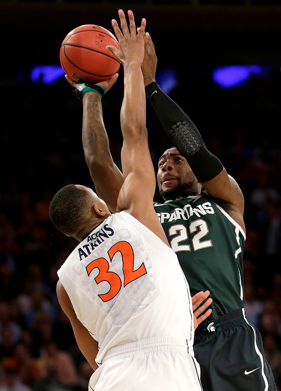 . Michigan State forward Branden Dawson (22) goes up for a shot against Virginia forward Darion Atkins (32) during the first half in a regional semifinal of the NCAA men\'s college basketball tournament, Friday, March 28, 2014, in New York. (AP Photo/Seth Wenig)
