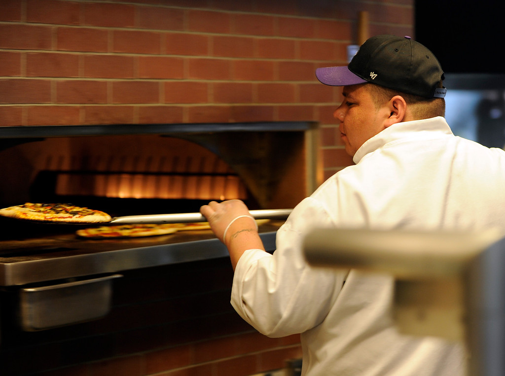 . Jonathan Martinez pulls a pizza pie from the brick oven  Denver  baseball park on May 3, 2013 before the Rockies game. (Photo By Cyrus McCrimmon/The Denver Post)