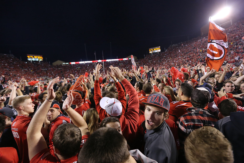 . SALT LAKE CITY, UT - OCTOBER 12: Fans and players of the Utah Utes celebrate their upset win over the Stanford Cardinal  during the first half of an NCAA football game October 12, 2013 at Rice Eccles Stadium in Salt Lake City, Utah. Utah Beat Stanford 27-21. (Photo by George Frey/Getty Images)