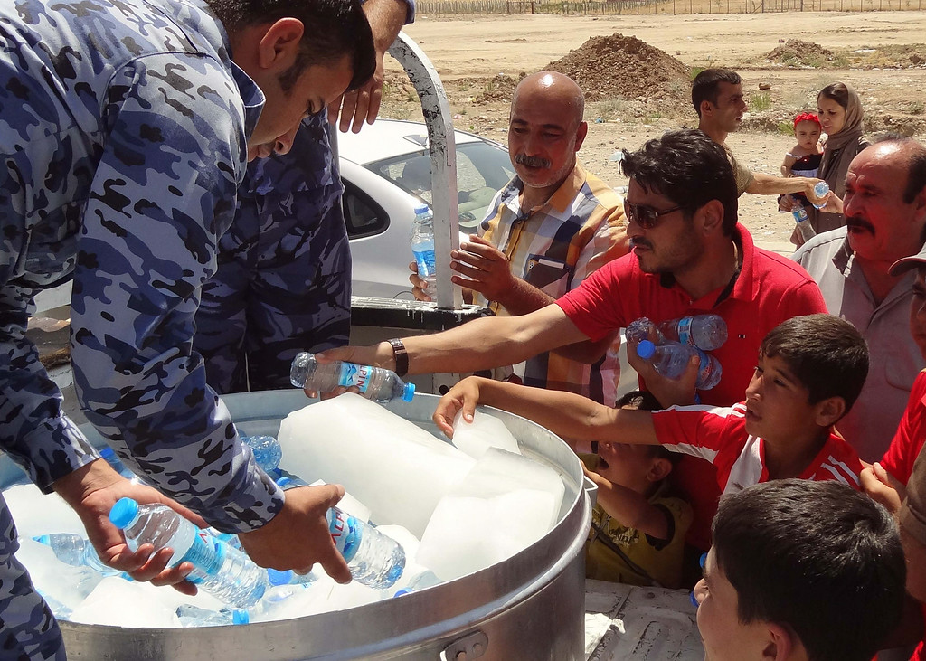 ". Iraqi military personnel distribute water to Shiite Iraqi Kurds, known as ""Shabak\"", displaced by fierce fighting between Kurdish peshmerga forces and jihadist militants from the Islamic State (IS) after arriving on the road between Kirkuk and Arbil having fled the area of Bartala near the northern Iraqi city of Mosul, on August 8, 2014. Jihadists seized Iraq\'s largest dam north of their hub of Mosul, giving them control over the supply of water and electricity for a vast area, officials said. AFP PHOTO / MARWAN IBRAHIM/AFP/Getty Images"