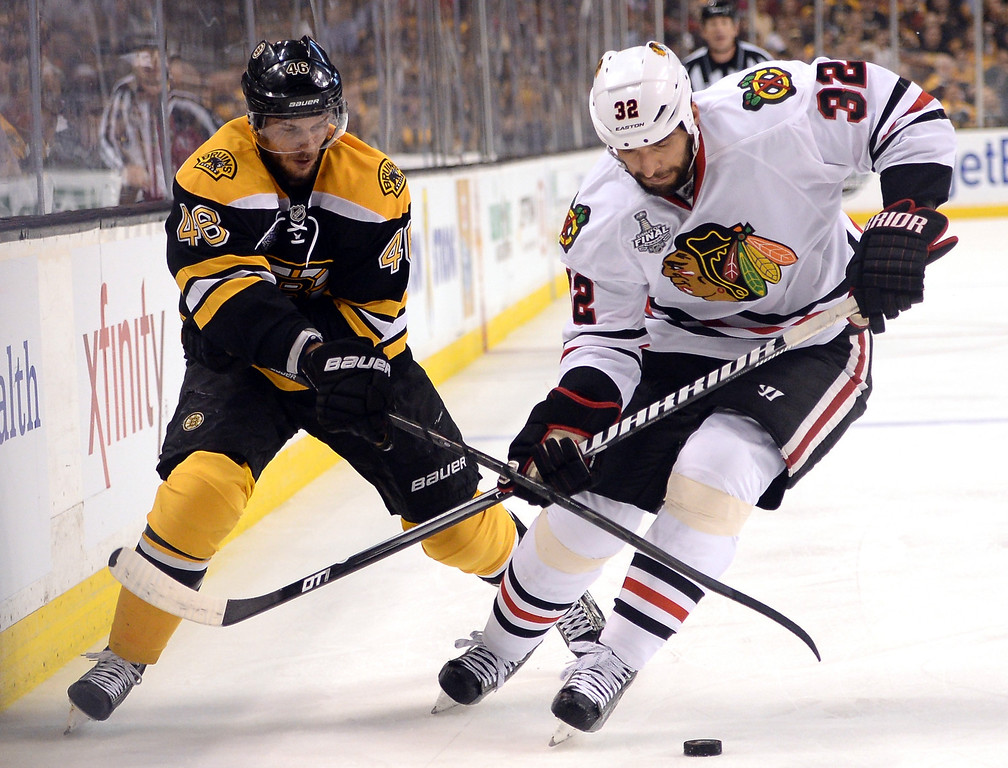 . Michal Rozsival #32 of the Chicago Blackhawks handles the puck as David Krejci #46 of the Boston Bruins defends during the first period in Game Four of the 2013 NHL Stanley Cup Final at TD Garden on June 19, 2013 in Boston, Massachusetts.  (Photo by Harry How/Getty Images)