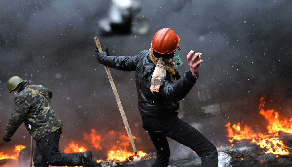 . A demonstrator throws a stone during clashes between protestors and police in the center of Kiev on January 22, 2014. AFP PHOTO / SERGEI SUPINSKY/AFP/Getty Images