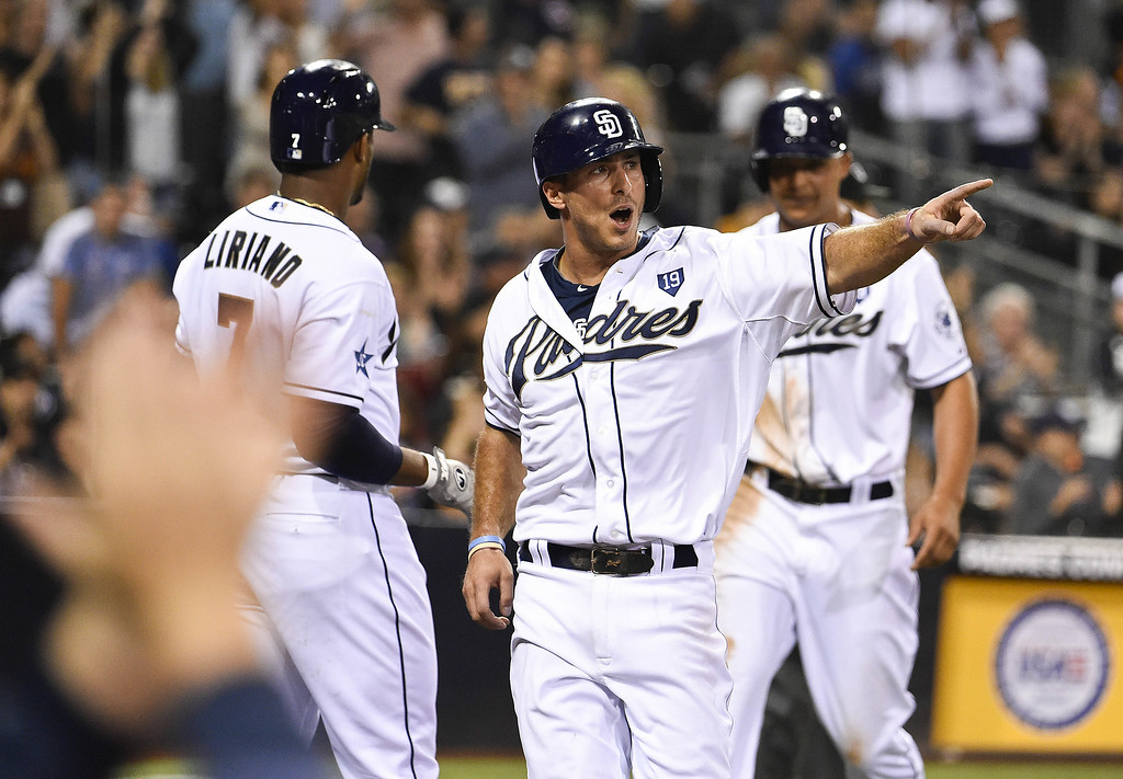 . SAN DIEGO, CA - AUGUST 12:  Tommy Medica #14 of the San Diego Padres celebrates after scoring during the eighth inning of a baseball game against the Colorado Rockies at Petco Park August, 12, 2014 in San Diego, California.  (Photo by Denis Poroy/Getty Images)