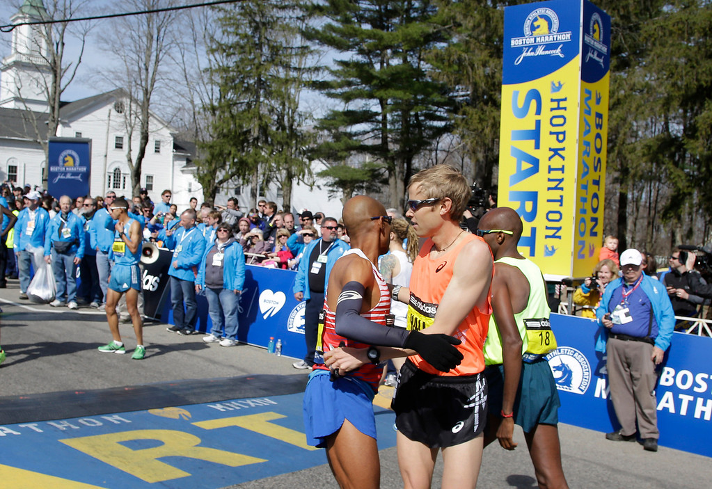 . Runners Meb Keflezighi, and Ryan Hall, right, of the United States, wish each other well before the start of 118th Boston Marathon Monday, April 21, 2014, in Hopkinton, Mass. (AP Photo/Stephan Savoia)