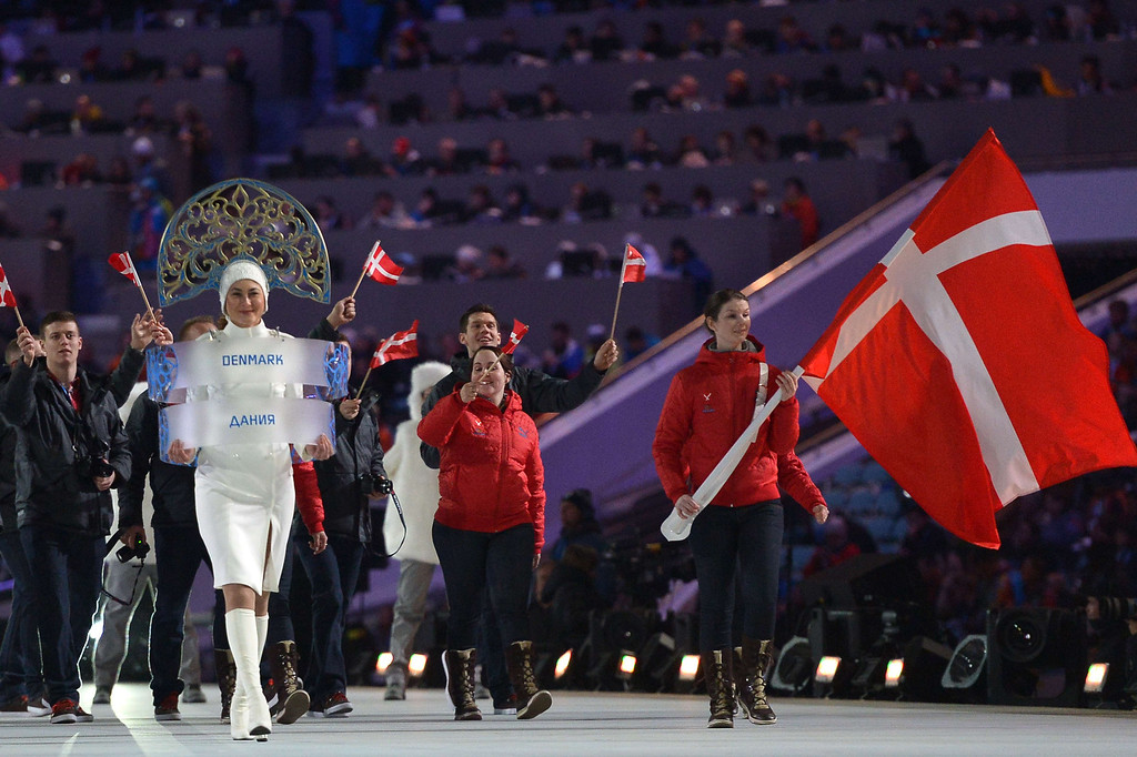 . Denmark\'s flag bearer, curler Lene Nielsen leads his national delegation during the Opening Ceremony of the Sochi Winter Olympics at the Fisht Olympic Stadium on February 7, 2014 in Sochi. AFP PHOTO / ALBERTO PIZZOLI/AFP/Getty Images