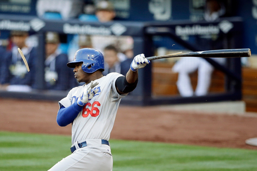 . Los Angeles Dodgers\' Yasiel Puig breaks his bat as he grounds out while playing the San Diego Padres during the third inning of an opening night baseball game on Sunday, March 30, 2014, in San Diego. (AP Photo/Gregory Bull)