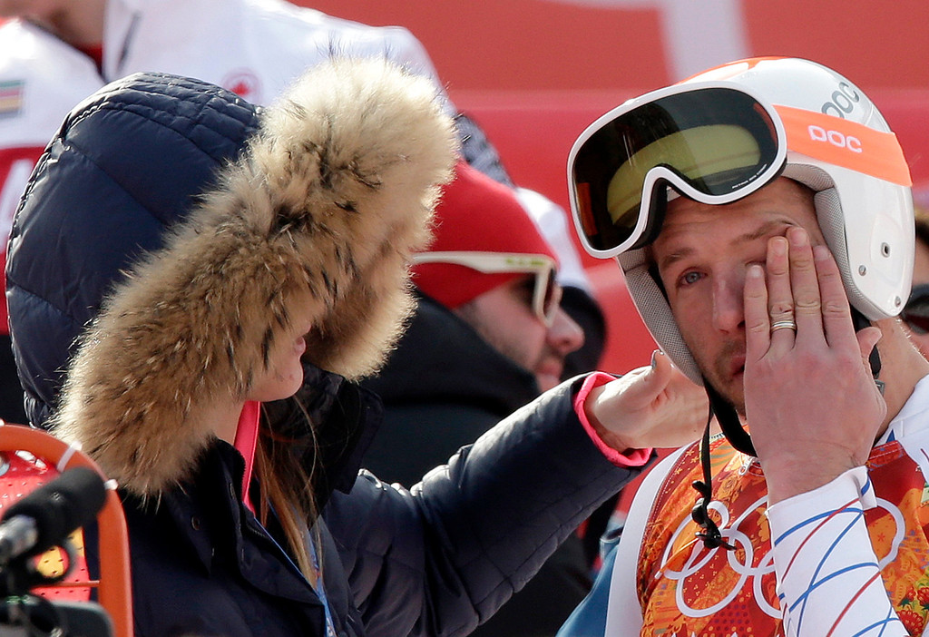 . United States\' Bode Miller wipes his face as he stands with his wife, Morgan, after finishing the men\'s super-G at the Sochi 2014 Winter Olympics, Sunday, Feb. 16, 2014, in Krasnaya Polyana, Russia. (AP Photo/Gero Breloer)