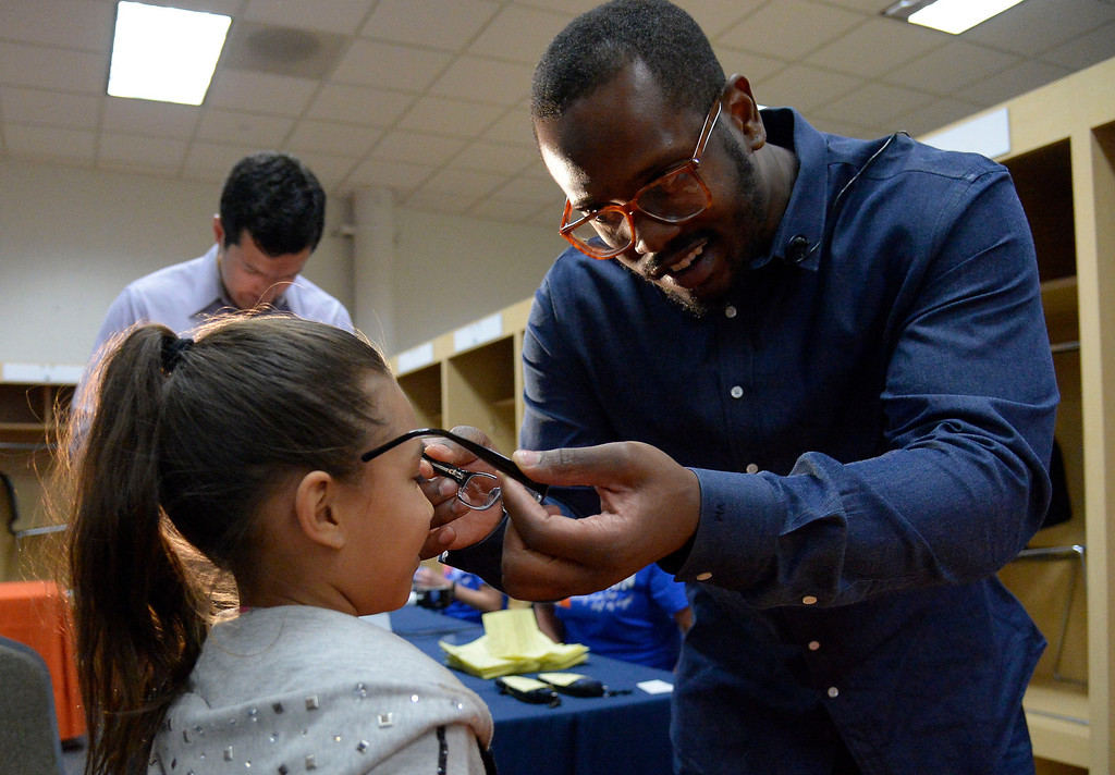 . Von Miller fits Mia Trevino, 10, with her new prescription glasses on Monday, April 14, 2014.   (Photo by John Leyba/The Denver Post)