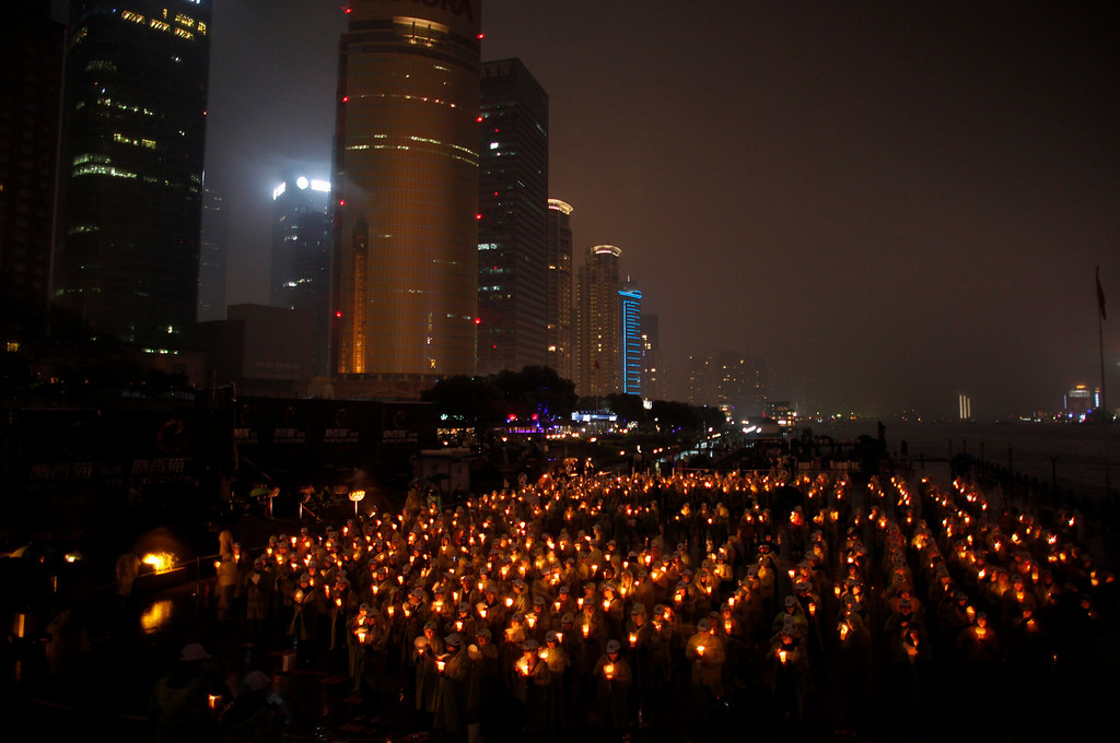 ". People hold candles during an event attempting to establish a Guinness World of Record for ""Blowing out the most number of candles simultaneously\"" during Earth Hour in Shanghai March 23, 2013. Earth Hour, when everyone around the world is asked to turn off lights for an hour from 8.30 p.m. local time, is meant as a show of support for tougher action to confront climate change. REUTERS/Carlos Barria"