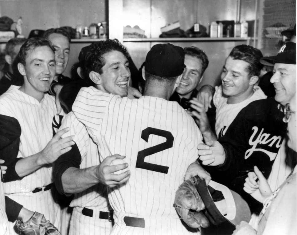 . New York Yankee Billy Martin gets a hug from coach Frank Crosetti (2) as his teammates gather around for a victory celebration at Yankee Stadium, Bronx, N.Y., Oct. 5, 1953.  Martin\'s hit in last of ninth inning drove in the run that won over the Brooklyn Dodgers, 4-3, in the sixth and deciding game of the 1953 World Series.  The win gives the Yankees their fifth straight Series championship.  From left are, Irv Noren, Andy Carey, Martin, Crosetti, Jim McDonald, Bill Miller and Ed Lopat, wearing cap.  (AP Photo)