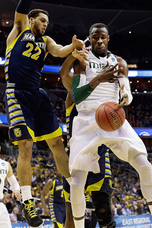 . Miami center Tonye Jekiri, right, loses control of the ball under pressure from Marquette guard Trent Lockett (22) during the first half of an East Regional semifinal in the NCAA college basketball tournament, Thursday, March 28, 2013, in Washington. (AP Photo/Pablo Martinez Monsivais)