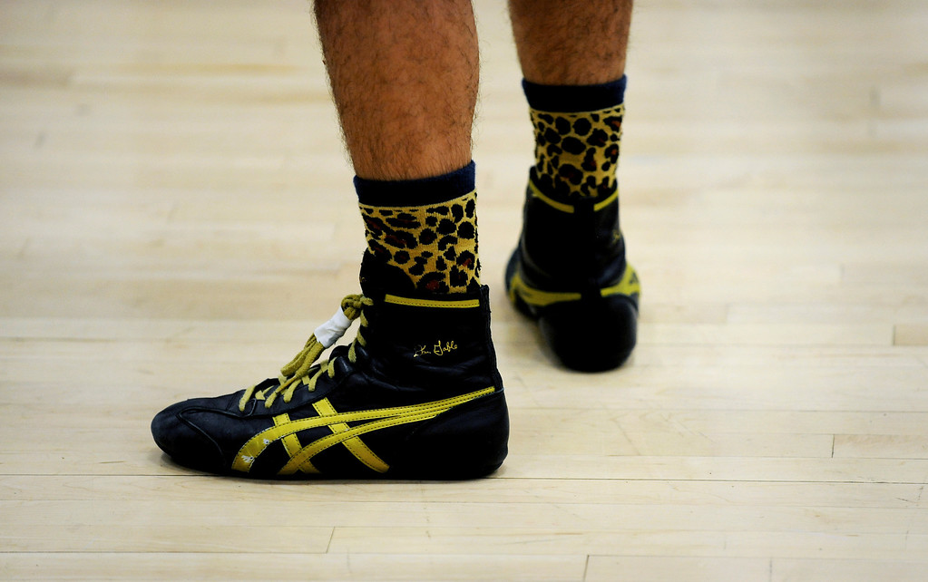 """. P.T. Garcia, 18, a senior at Bear Creek High School, sports his cheetah socks during the Commanders Invitation Wrestling Tournament. Garcia said he wanted to be \""""fast like a cheetah today,\"""" so he wore the appropriate socks. Photo by Jamie Cotten, Special to The Denver Post"""