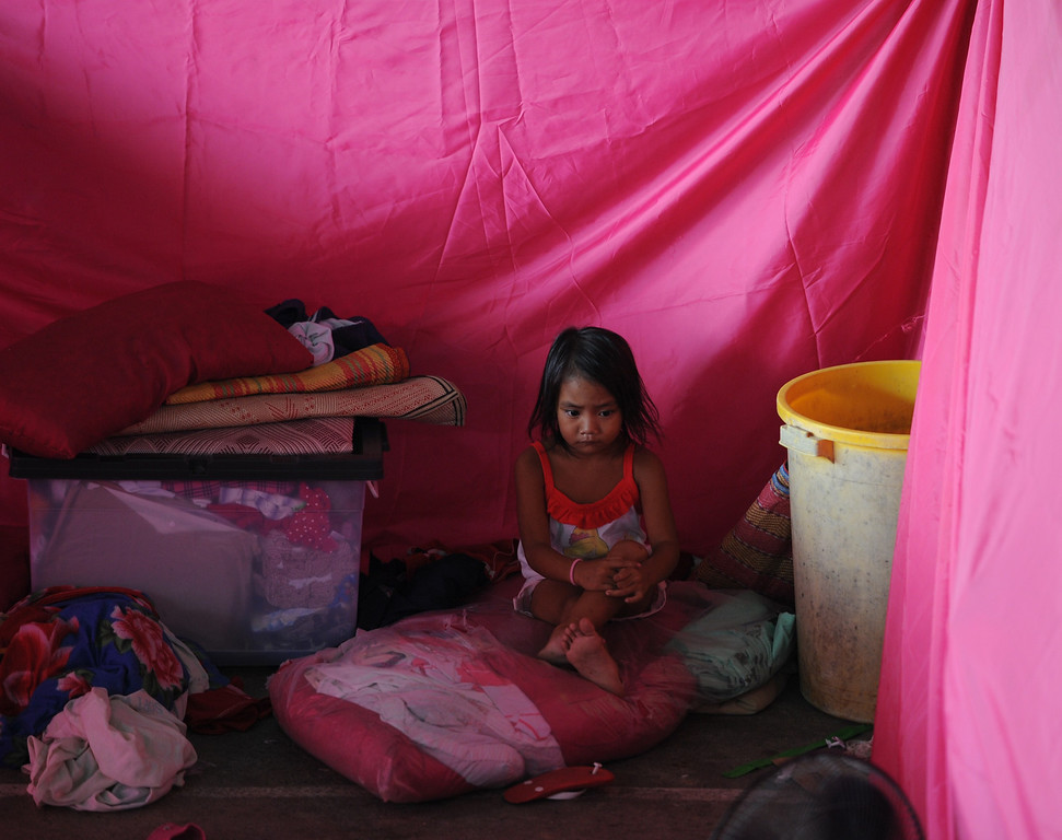 . A little girl affected by flooding due to heavy rains exarcebated by Tropical storm Trami sits inside temporary shelter at a basketball gym serving as an evacuation center in the town of Calumpit, Bulacan province, north of Manila on August 22, 2013. Disaster-weary Philippine residents mopped up August 22 after four days of rains that officials said had killed 18 people and forced more than half a million from flooded homes. TED ALJIBE/AFP/Getty Images