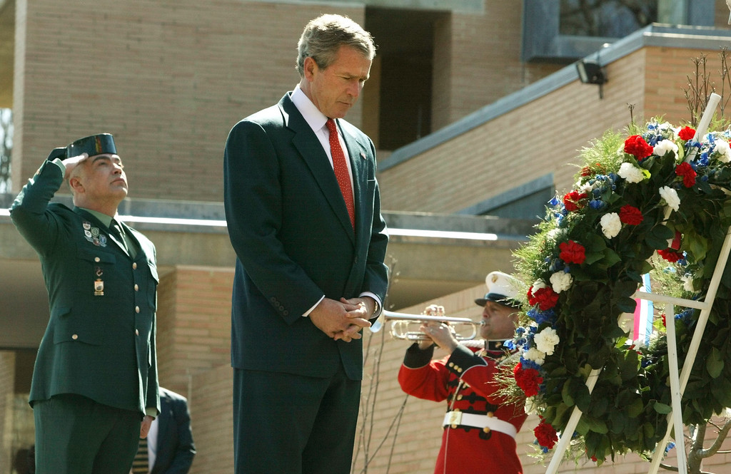 """. U.S. President George Bush, center, bows his head during the playing of \""""Taps\"""" after laying a wreath for the victims of the railway bombings in Madrid, Spain at the Spanish ambassador\'s residence Friday, March 12, 2004 in Washington. (AP Photo/Charles Dharapak)"""