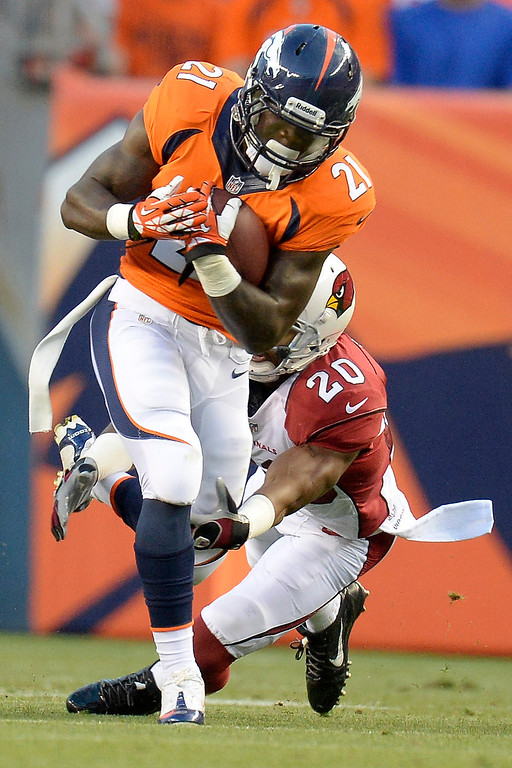 . Denver Broncos running back Ronnie Hillman (21) runs through a tackle by Arizona Cardinals cornerback Antoine Cason (20) during the first half on August 29, 2013 at Sports Authority Field at Mile High.  (Photo by John Leyba/The Denver Post)