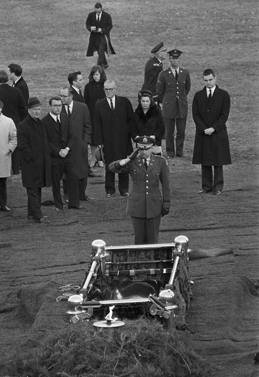 . A military officer salutes Kennedy\'s grave as the Eternal Flame burns at Arlington National Cemetery on Nov. 25, 1963.  Associated Press file