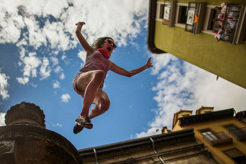 ". A reveler jumps from a fountain onto the crowd below, after the launch of the \'Chupinazo\' rocket, to celebrate the official opening of the 2014 San Fermin fiestas in Pamplona, Spain, Sunday, July 6, 2014. Revelers from around the world turned out here to kick off the festival with a messy party in the Pamplona town square, one day before the first of eight days of the running of the bulls glorified by Ernest Hemingway\'s 1926 novel ""The Sun Also Rises.\"" (AP Photo/Andres Kudacki)"