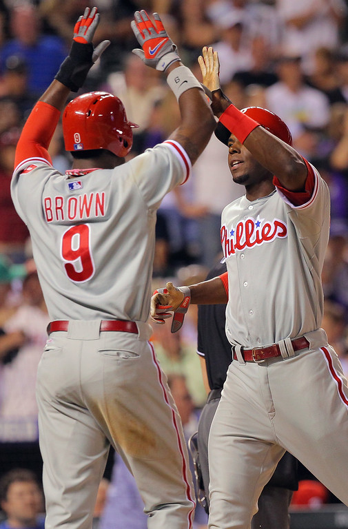 . DENVER, CO - JUNE 14:  Domonic Brown #9 of the Philadelphia Phillies and John Mayberry Jr. #15 of the Philadelphia Phillies celebrate as they score on a triple by Freddy Galvis #13 of the Philadelphia Phillies off of Wilton Lopez #59 of the Colorado Rockies to tie the score 7-7 in the seventh inning at Coors Field on June 14, 2013 in Denver, Colorado.  (Photo by Doug Pensinger/Getty Images)